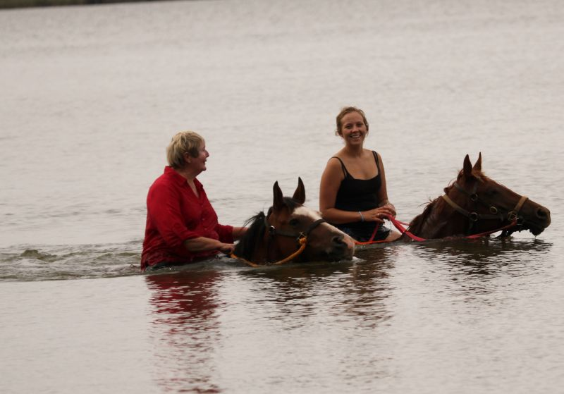 Lesley & Breanna Hargrave swimming Tango and Caprice in lake.